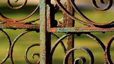 Ржавчина на кованых изделиях, распространяющаяся под слоем застарелой краски.
