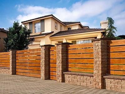 Деревянный забор, опирающийся на бетонные конструкции.